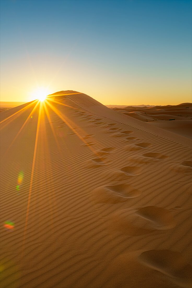 Sunrise over a dune in the Sahara Desert. This is part of the Morocco bike tour that stops at the Erg Chebbi Dunes for two days.