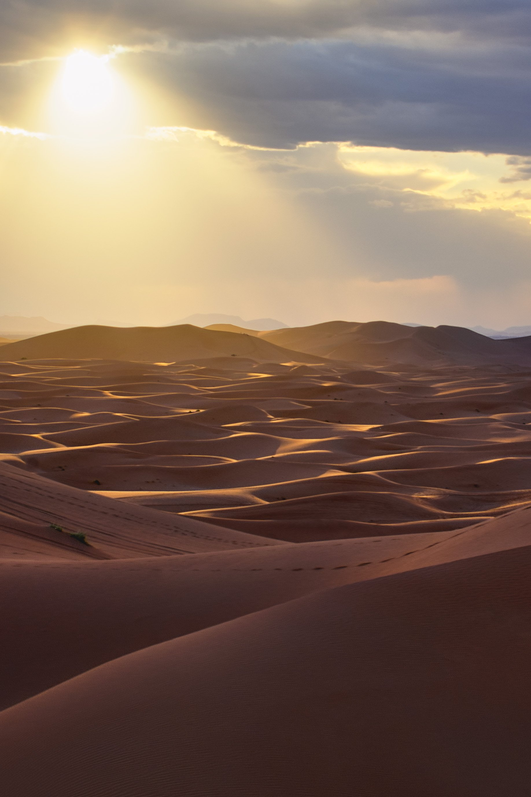 A storm over Erg Chebbi Desert in the Sahara Desert of Morocco paints the dunes in soft light moments before we run for cover from the rain.